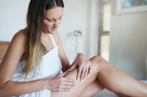 Woman looking at her legs, upset at her cellulite